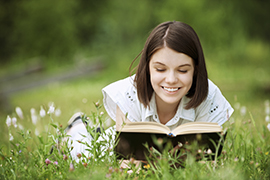 Young lady reading book in a garden