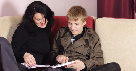 Mother and son referring a book